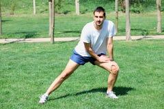 Hombre que estira los músculos en el parque de la ciudad Foto de archivo
