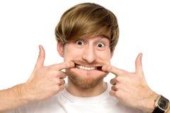 Hombre que estira su boca Imagen de archivo