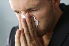 Hombre que estornuda Imagen de archivo libre de regalías