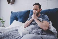 Hombre que estornuda en servilleta foto de archivo