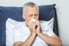 Hombre que estornuda en servilleta fotografía de archivo