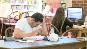 Hombre que estudia en la biblioteca almacen de metraje de vídeo