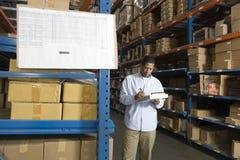 Hombre que examina las cajas en Warehouse Imagenes de archivo