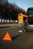 Hombre que examina los coches dañados del automóvil después de romper Imagen de archivo libre de regalías