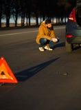 Hombre que examina los coches dañados del automóvil después de romper Foto de archivo libre de regalías