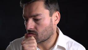 Hombre que experimenta dolor y la tensión Hombre joven frustrado en camisa y lazo que dan masajes a la nariz y que guardan rato c metrajes