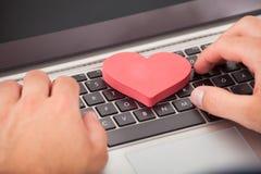 Hombre que fecha en línea en el ordenador portátil fotos de archivo libres de regalías