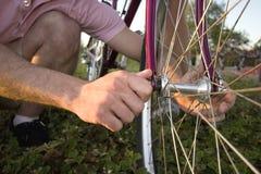 Hombre que fija una bici - horizontal fotografía de archivo libre de regalías