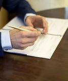 Hombre que firma un documento Imágenes de archivo libres de regalías