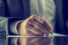 Hombre que firma un documento o que escribe correspondencia imagen de archivo libre de regalías