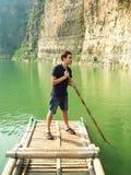 Hombre que flota en una balsa de bambú Imágenes de archivo libres de regalías