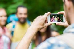 Hombre que fotografía a amigos por smartphone Imágenes de archivo libres de regalías