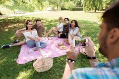 Hombre que fotografía a amigos por smartphone en la comida campestre Imagen de archivo libre de regalías