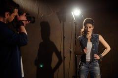 Hombre que fotografía a la muchacha en estudio fotos de archivo