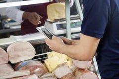 Hombre que fotografía a través de la tableta de Digitaces en tienda del queso Fotografía de archivo