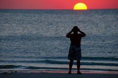 Hombre que fotografía una puesta del sol colorida del océano Imágenes de archivo libres de regalías