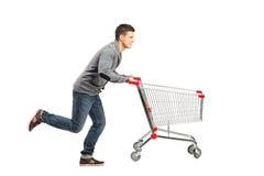 Hombre que funciona con y que empuja un carro de compras Imagen de archivo libre de regalías
