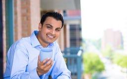 Hombre que goza de la bebida en balcón exterior Imagen de archivo libre de regalías