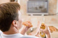 Hombre que goza de la cerveza y de la pizza delante de la TV Imagen de archivo libre de regalías