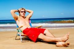 Hombre que goza de Sunny Day en la playa Imagenes de archivo