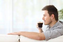 Hombre que goza de una taza de café en casa Foto de archivo libre de regalías