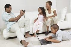 Hombre que graba a la familia que se sienta en el sofá imágenes de archivo libres de regalías