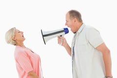 Hombre que grita en su socio a través del megáfono Imagenes de archivo