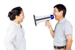 Hombre que grita en su socio a través del megáfono Fotos de archivo
