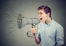 Hombre que grita en un megáfono que hace el aviso Foto de archivo