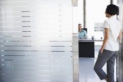 Hombre que habla con la mujer que se coloca en entrada de la oficina fotografía de archivo