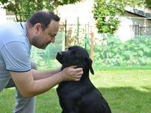 Hombre que habla con su perro Foto de archivo libre de regalías