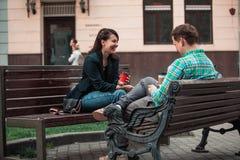 Hombre que habla de risa con la mujer que se sienta en el caf? de consumici?n del banco que practica surf en Internet Forma de vi foto de archivo libre de regalías
