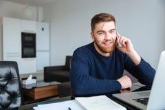 Hombre que habla en el teléfono en casa Imagenes de archivo