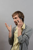 Hombre que habla en el teléfono En un gris Imagen de archivo libre de regalías
