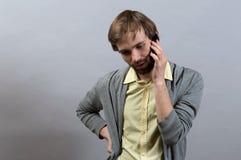 Hombre que habla en el teléfono En un gris Fotografía de archivo libre de regalías