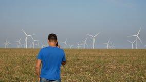 Hombre que habla en el teléfono móvil cerca alrededor de la producción de electricidad de las turbinas de viento, concepto verde  metrajes