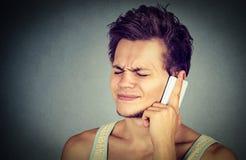 Hombre que habla en el teléfono móvil que tiene dolor de cabeza Imagenes de archivo