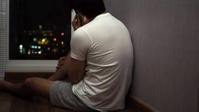 Hombre que habla en el teléfono, y el sentarse por una ventana en la noche almacen de video