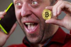 Hombre que habla en el tel?fono que lleva a cabo el bitcoin foto de archivo libre de regalías
