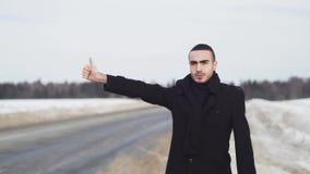 Hombre que hace autostop en la carretera nacional del invierno con el autoestop plateMan de la cartulina en la carretera nacional metrajes
