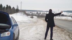 Hombre que hace autostop en la carretera nacional del invierno con la placa de la cartulina metrajes