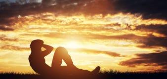 Hombre que hace crujidos al aire libre en la puesta del sol Fotografía de archivo libre de regalías