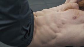 Hombre que hace ejercicio del ABS y que dobla su caja de seis Músculos de bombeo del hombre atlético almacen de metraje de vídeo