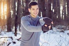 Hombre que hace ejercicio del deporte en invierno del bosque Foto de archivo