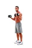 Hombre que hace ejercicios con pesas de gimnasia Imágenes de archivo libres de regalías