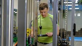 Hombre que hace ejercicios del tr?ceps en el gimnasio almacen de metraje de vídeo