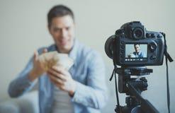 Hombre que hace el blog video sobre la ganancia del dinero Foto de archivo libre de regalías