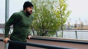 Hombre que hace el ejercicio para el ABS en parque Hombre atlético joven vestido en la ropa de los deportes, haciendo ejercicio e almacen de metraje de vídeo