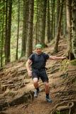 Hombre que hace el rastro que corre en el bosque Foto de archivo libre de regalías