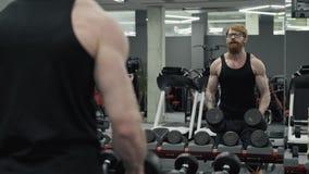 Hombre que hace elevación-UPS, llevando a cabo pesas de gimnasia en manos, entrenamiento para los músculos del hombro metrajes
